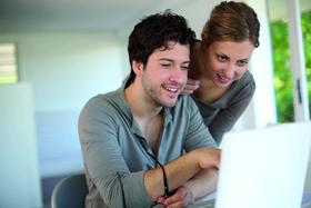 Paar, das am Rechner ein Stipendium auswählt